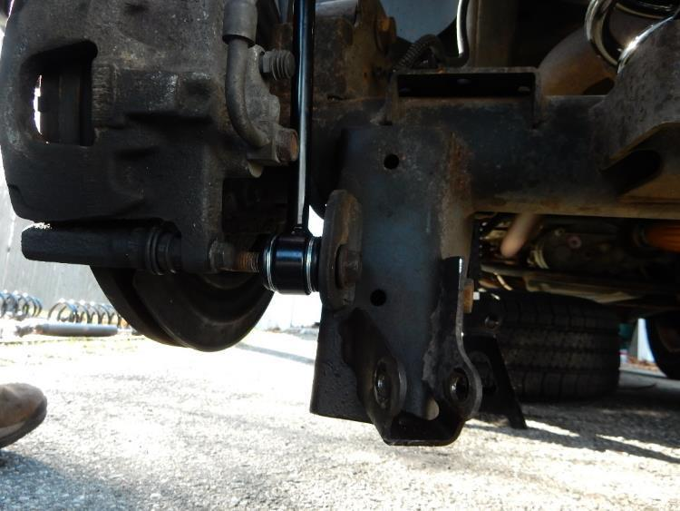 22. Using an 18mm socket and wrench, reinstall the factory bolt and nut to attach the axle side of the sway bar link to the axle bracket on