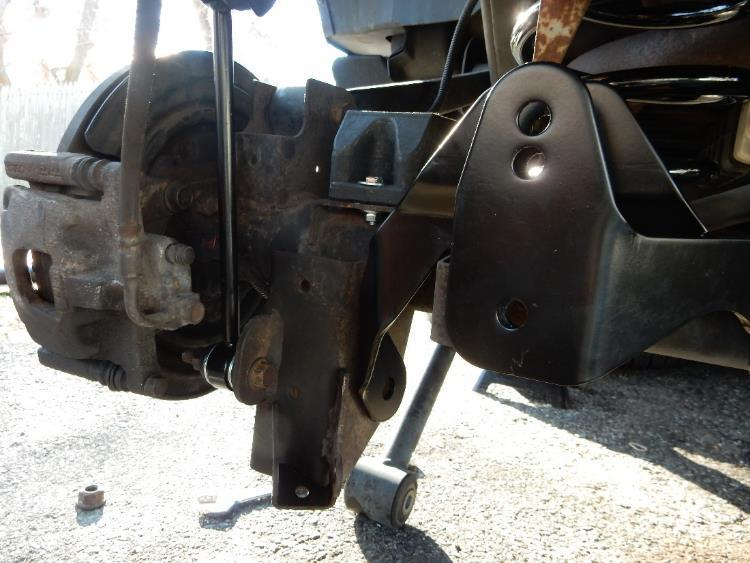 Position the rear axle track bar bracket over the