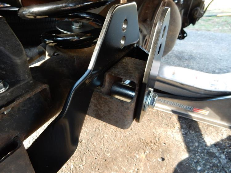 Position the provided spacer sleeve between the factory track bar bracket and the axle track bar bracket.
