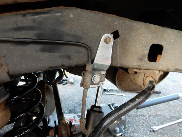 Using a 7/16 socket and wrench, install the supplied bolts, washers, and nuts to attach the factory brake line bracket to the brake line extension bracket on the driver and
