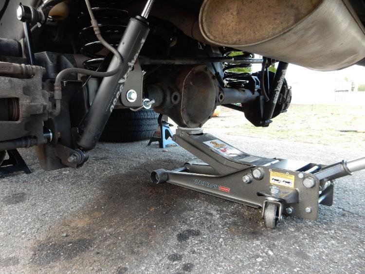 Using the floor jack, carefully lower the front axle far enough to remove
