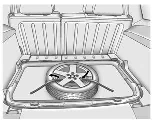 Vehicle Care 10-79 6. Route the strap through the wheel, as shown. 7. Attach the strap to the other cargo tie-down in the rear of the vehicle. 8. Tighten the strap. 9. Replace the rubber cover.