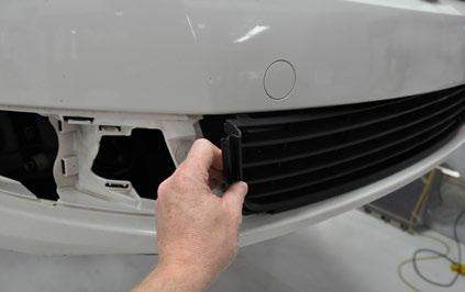 MOUNTING THE FOG LAMPS Step 3: Starting on one side, gently pull out the top of the center grille until the upper clips release from the bumper cover.