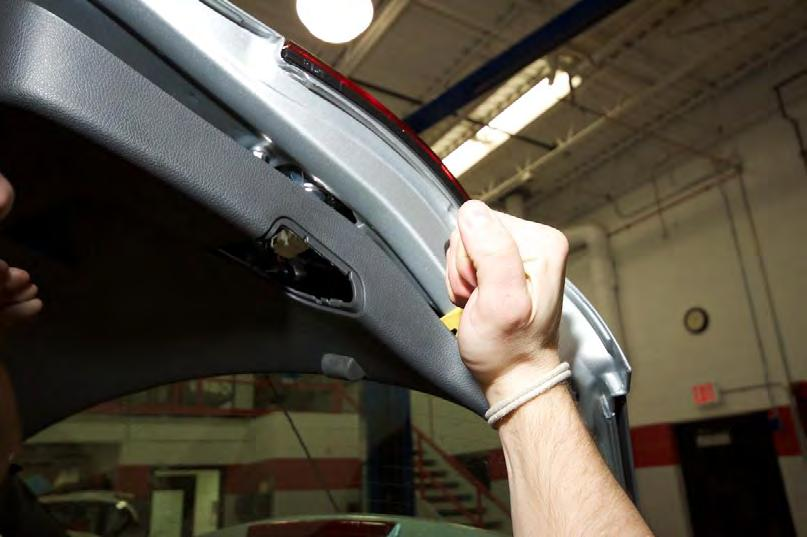 Install the Camera Step 1-3 Pry the rear hatch trim panel away from the hatch using a plastic,