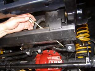 11. Pass caged nut plate from top through crossmember, then upwards into open end of chassis rails. 12.