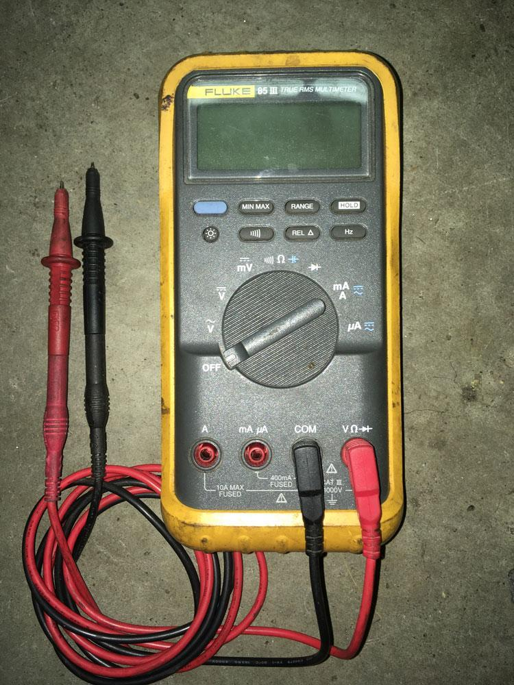 The familiar layout of a multimeter with display, option buttons, rotary dial, and plug sockets.