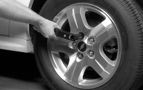 Removing the Flat Tire and Installing the Spare Tire 1. If your vehicle has a wheel cover or hubcap that has plastic wheel nut caps, loosen the plastic nut caps.