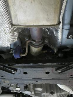 With the brace removed, use a 15mm box wrench to break loose the nuts that secure the downpipe to