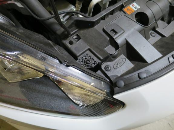 6. With the hardware removed from each headlight, carefully pull it up and out of the vehicle. Make sure to disconnect the electrical connector to allow it to be completely removed. 7.