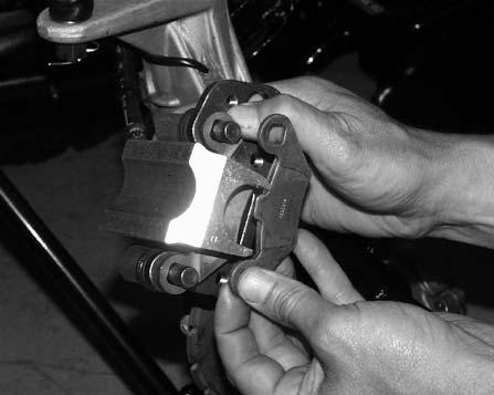 Remove caliper from mounting bracket. 4. Push caliper piston into caliper bore slowly using a C-clamp or locking pliers with pads installed.