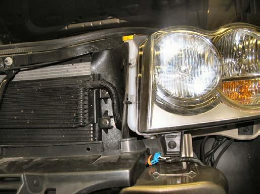 Remove two (2) christmas tree pushpins from the washer reservoir spout and air dam just inside of the headlight