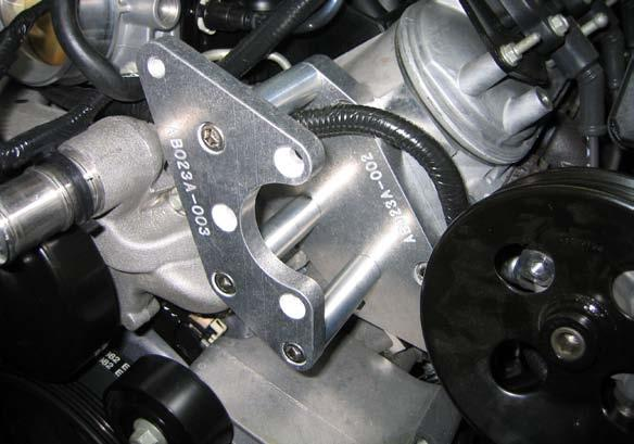 5 Mount the supplied power steering pump relocation bracket to the subbracket, spacing