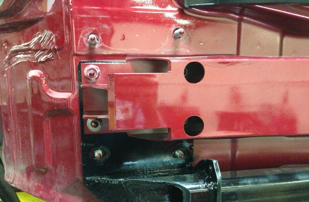 Place the impact bar back over the trailer hitch plate and replace the four nuts removed in Step 16 with the supplied M10x1.5 serrated flange nuts.