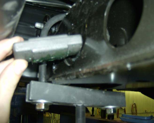 9. Working on the driver side, carefully tap the torsion bar forward until the torsion bar key can be