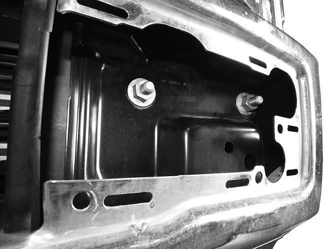 From behind bumper, release metal clips attaching plastic