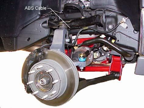 4) Apply thread lock to original bolts and attach the hub and bearing assembly to the left steering knuckle. Refer to illustration #13. Tighten the mounting bolts to 133 ft. lbs.