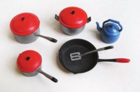 All the pots and the egg flip have black paint on the tips of the handles. The frying pan has a red paint tip on its handle and is spray painted with black paint on the front.