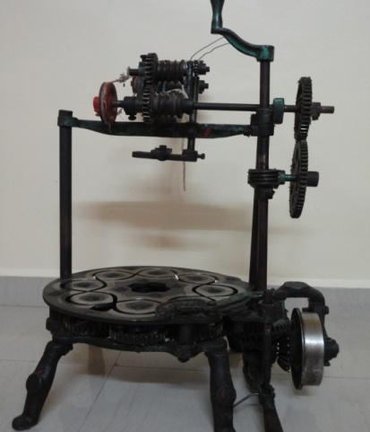 motion to bobbins mounted on the top plate by transmitting the power to the gear train assembled below the top plate.
