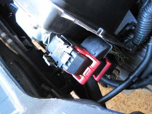 3. Unplug the two ECU wire harnesses by depressing tabs and rotating red levers.
