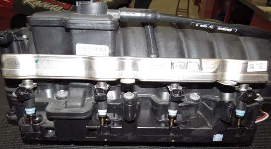 Using a 14mm deep socket, remove the fuel rails from the factory intake manifold. (6.