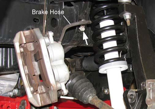 Attach the front caliper to the steering knuckle with the original mounting bolts. Tighten the caliper mounting bolts to 130 ft. lbs. 4) Remove the brake hose banjo bolt at the caliper.