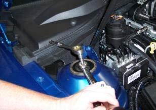 5. Loosen the nut on top of the strut underneath the hood.