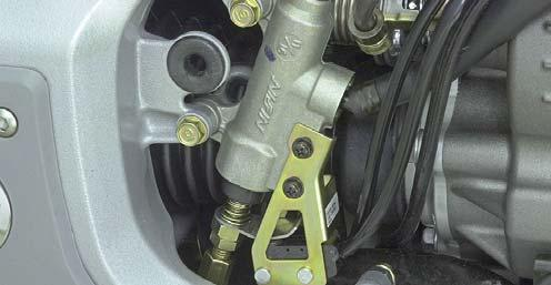 Remove the right engine side cover. Look for a punch mark on the rear master cylinder lower mounting tab as shown.