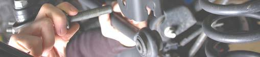Using a 14mm wrench unbolt the top of the shock and remove. See Photo 3.