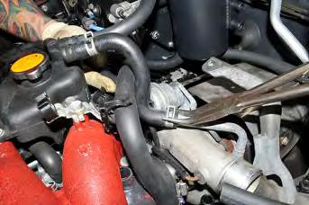 Remove the upper OEM coolant line pinch clamp and pull the OEM line off the