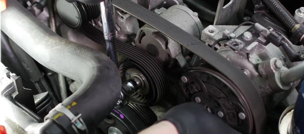 Release the harness clips that secure the alternator cable and disconnect the electrical harness