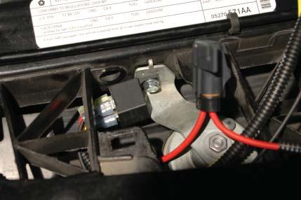 97. Use a 10mm wrench to remove the bolt from the passenger side horn mount.