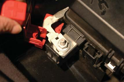 101. Remove the red wire cover from the positive (+) terminal on the outside of the fuse center box by