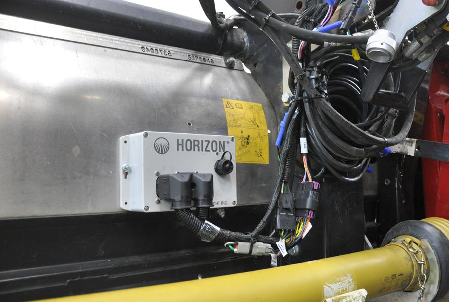 Hold the box at rear of header as shown and make sure Headsight harness can reach feeder house