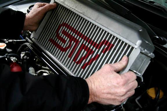 Carefully pull the intercooler up and out of the engine bay.