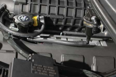 The embossed arrow on the top of the valve points toward the driver side fender.