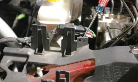 Use an 18mm wrench to remove the nuts securing the strut tower brace in position (two each side).