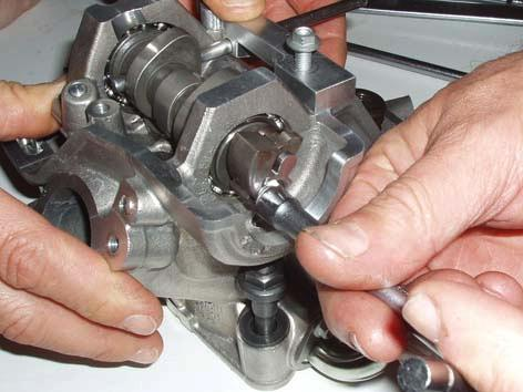 Remove the exhaust valve rocker arm shaft snap ring.