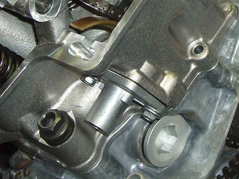 ENGINE Engine 450-550 Install the chain tensioner as follows: 1 Remove the chain tensioner threaded plug and spring.
