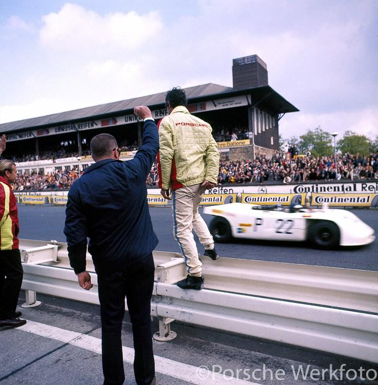 Nürburgring 1000 km, 31 May 1970: Vic Elford stands on the Armco barrier as teammate Kurt Ahrens crosses the