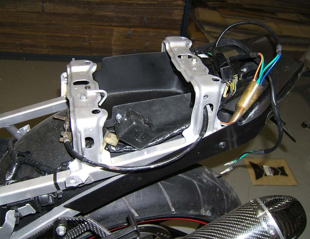 Disconnect all electrical components such as CDI, regulator and fuse box as well as the luggage hooks at the rear on the left and right.